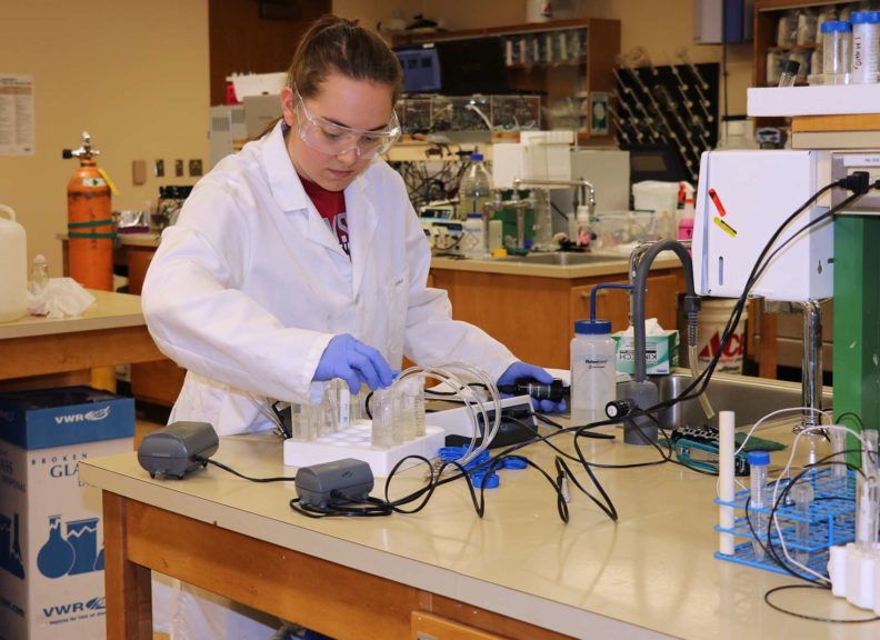 student in lab coat working in lab with vials of chemicals and other equipment