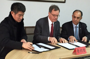 Yunsheng Ma, chairman of Shandong Petrochemical Co. Ltd., left, and WSU's Chris Keane and Asif Chaudhry sign the agreement in China.
