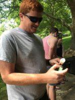 Student at BBQ holding lighter under marshmallow