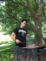 Student cooking food over outdoor grill