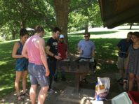 WSU REU Program students socializing at park around grill