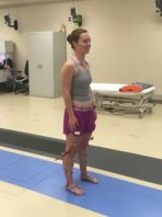 Female student stands on mat in lab with sensors attached to her feet, calves, and knees