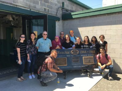 WSU REU Program students pose with Hanford Reactor sign in Richland, WA (sign text: Reactor 1944-1968, World's first full scale nuclear reactor, American Nuclear Society)