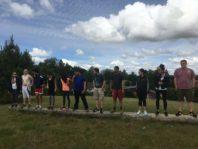 Chemical engineering students standing on log for WSU REU Program Rec challenge