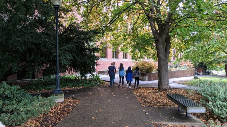 WSU Voiland School exterior with students walking and trees in fall