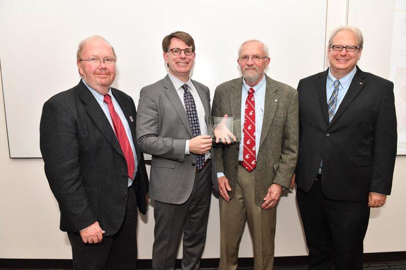 Dr. James Petersen, Dr. Christopher Jones, David Ensor, and Dr. Jean Sabin McEwen posing with the award given to Dr. Christopher Jones.