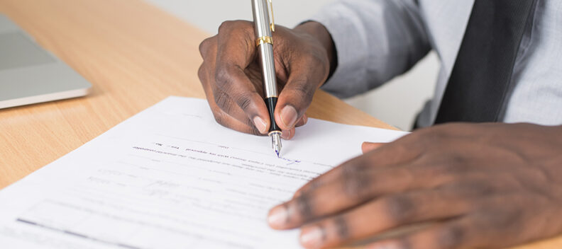 Hands with pen filling out form