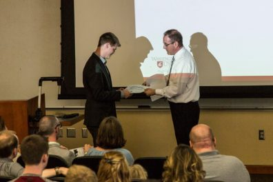 Dr. Hughes giving Jansen VanderMeulen his certificate for DFLC Outstanding Senior.