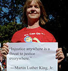 "Sue Peabody holds sign with MLK quote ""Injustice anywhere is a threat to justice everywhere."""