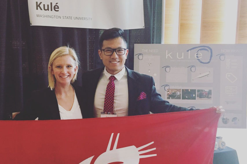 Miller and Charoonsophonsak holding WSU Cougar flag in front of their Kule booth display