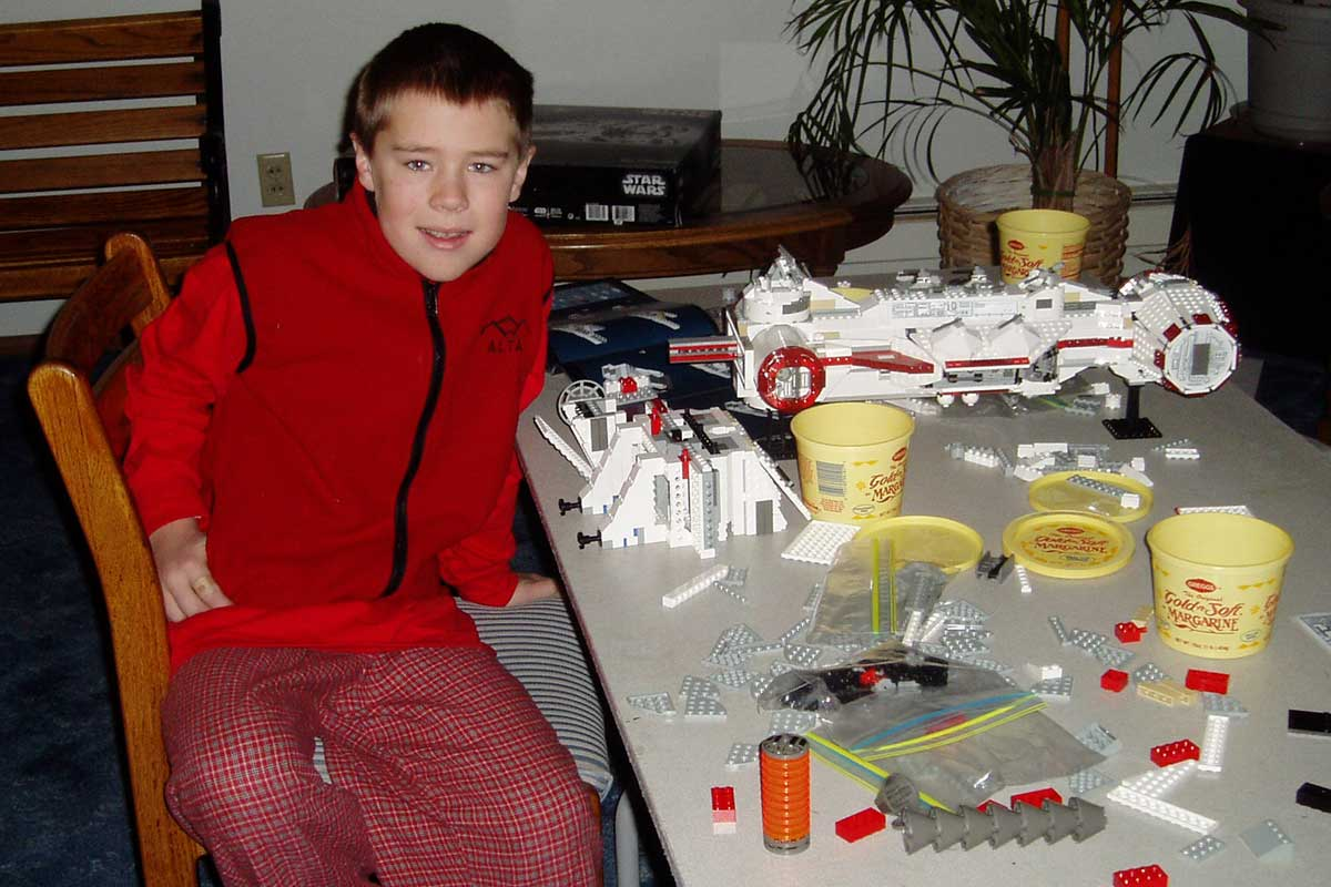 Summers as a youth sitting at a table covered with Legos
