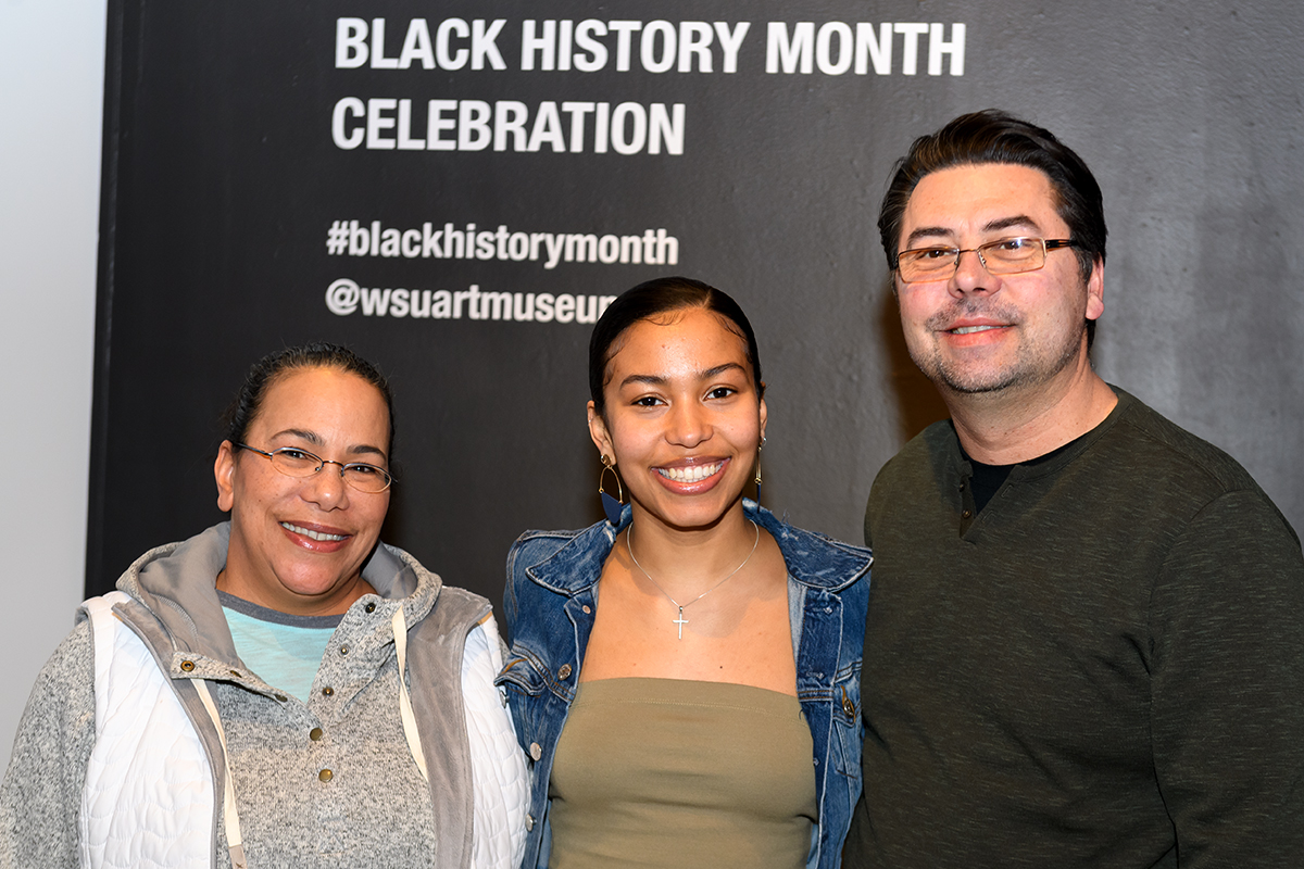 Murphy poses with her parents in front of 'Black History Month Celebration' sign.