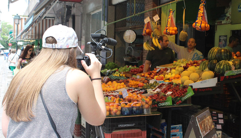Student with camera in front of fruit vendor