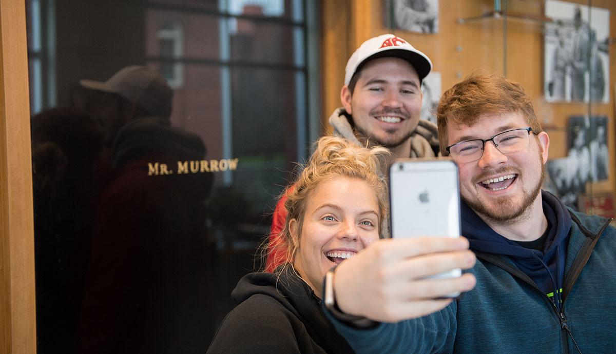 Students taking selfie in front of Murrow door