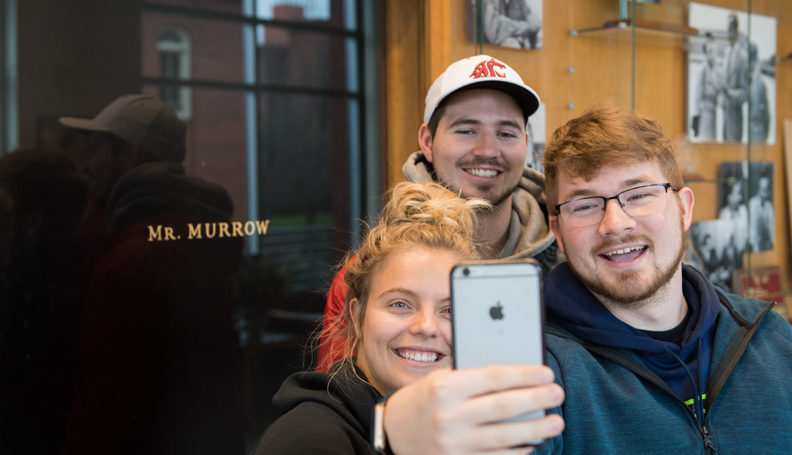 Students taking selfie in front of Murrow door