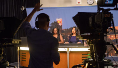 Students in Murrow News 8 studio carrying out news braodcast
