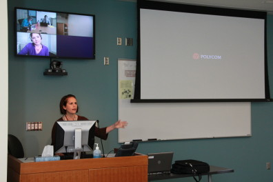 Instructor lecturing in front of a pull-down screen
