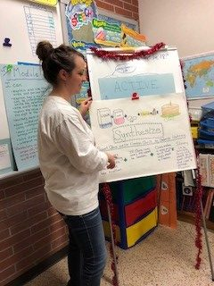 Masters student Amy Jacobson standing at flip chart teaching in classroom.