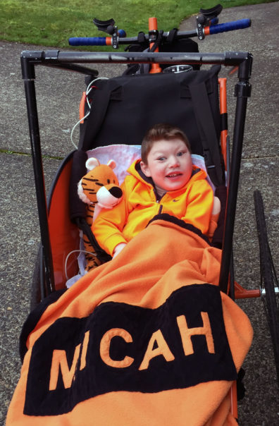 Micah sitting in bicycle front cart