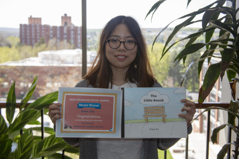 Grace Ku holding her book and winning certificate