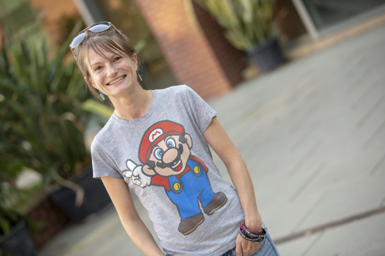Ashley Vaughan standing outside the Education Addition building. She's wearing a Super Mario T-shirt.