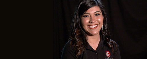 Andrea Castillo smiling with pitch black backdrop.