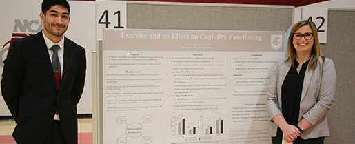 two people standing at the sides of a large academic poster