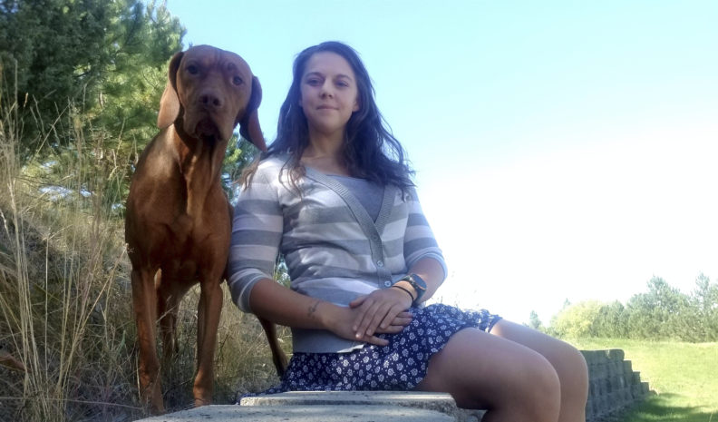 Hallie Music sitting next to her standing dog.