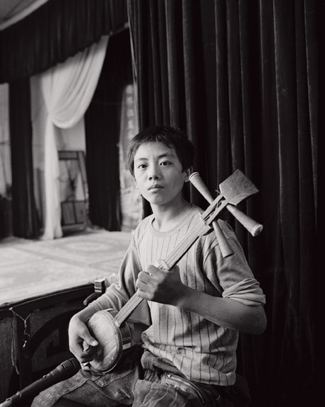 The performers are usually accompanied by a small group of musicians. Here a boy plays a sanxian, a traditional three stringed instrument.