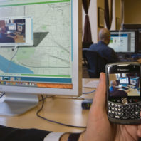 Orest Piskalns uses his BlackBerry to photograph co-worker Kevin Karpenske '08 and show how MapWith.Us technology works. He uploads an image and then, using the phone's Global Positioning System coordinates, pinpoints Karpenske's location.