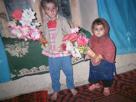 Children of Laghman look surprised as their picture is taken while showing off beautiful fabric flowers.