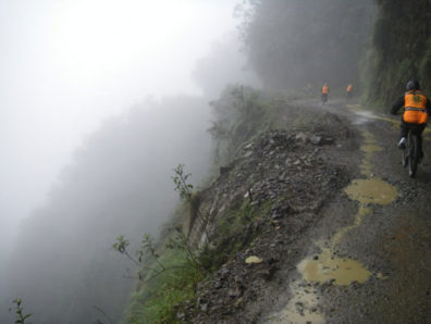 "The ""World's Most Dangerous Road,"" in Bolivia, offers spectacular views and landscapes as well as spectacular weather. Here a group rides down through a rain storm. Courtesy Derren Patterson"