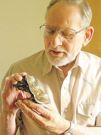 Carl Gustafson holds a mastodon tooth