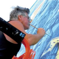Pat Siler works on mural in downtown Pullman