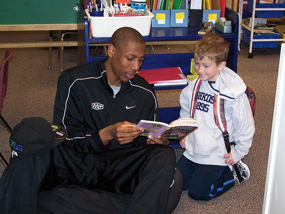 WSU basketball player Marcus Capers reading with a kid
