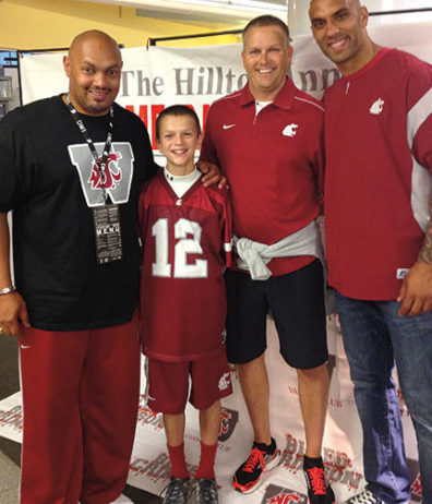 Derek Sparks '95 (left) and Mkristo Bruce '06 (right) pose with Coug fans on a September weekend when dozens of football players came back to campus. Courtesy Derek Sparks