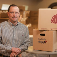 Dave Wilson '86 with WSU-themed boxes for graduates, produced by Spokane Packaging. Photo Robert Hubner