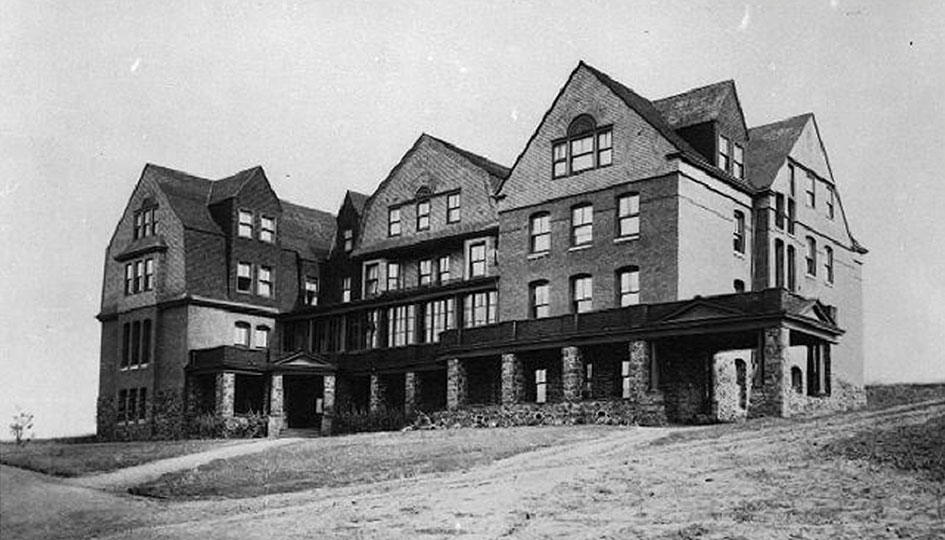 Stevens Hall, c. 1898 - Completed in 1896, Stevens Hall was named after the first governor of Washington Territory. A view of the West facade of the dormitory designed by Stephen and Josenhans in a colonial style and faced with basaltic rock, brick made on campus, and wood shingles. Dirt paths surround the structure.