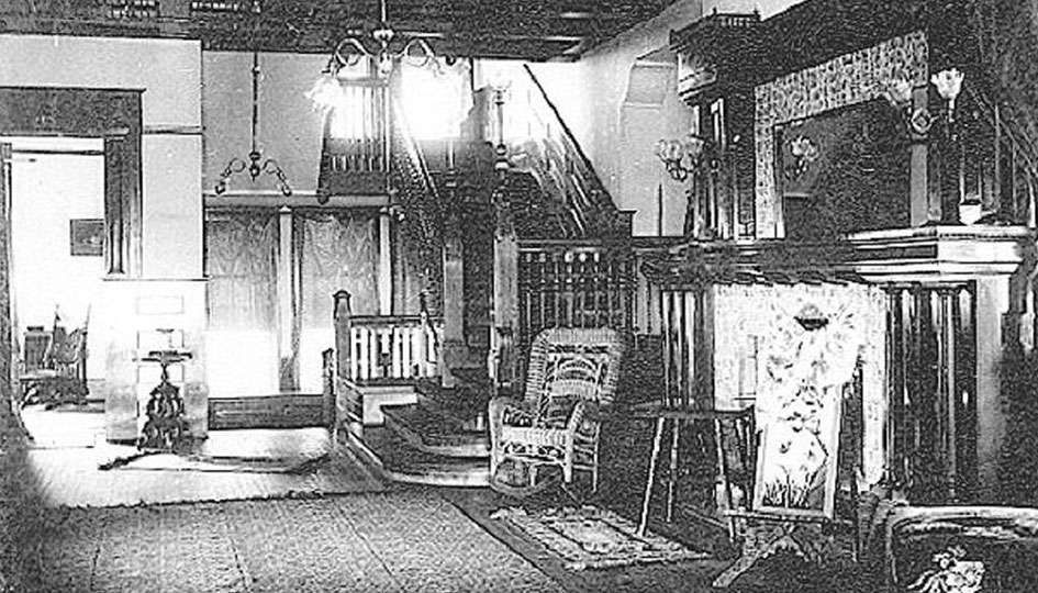 Stevens Hall interior, c. 1910 - An interior view the ladies drawing room. A stair case lead to the second floor. The coffered wooden ceiling, wicker chairs, and a fireplace are evident.