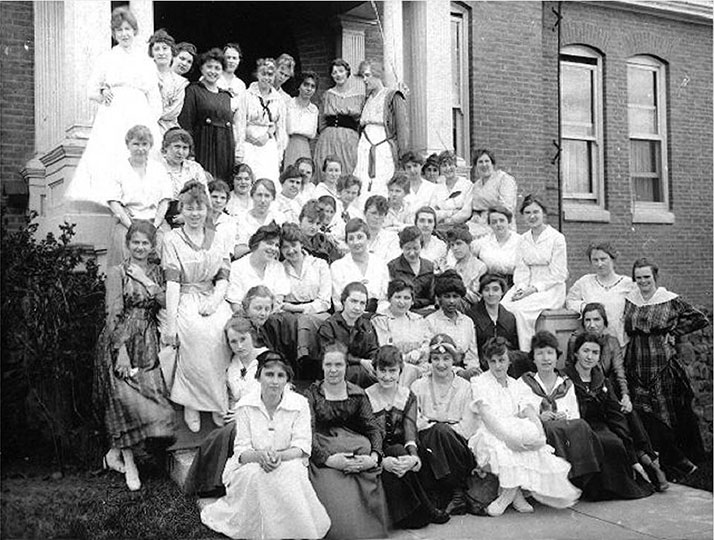 Stevens Hall women, c. 1920 - Photographer Myron Huckle. A posed group portrait of female students, arranged in six rows, on the steps of Stevens Hall.
