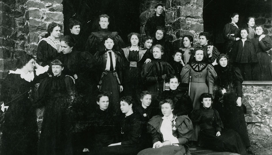 Stevens Hall women, 1896 - A posed group portrait of female students wearing black dresses, arranged on the steps of Stevens Hall.