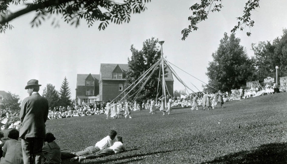 Dance around the maypole - Photographic image of women dancing around maypole on lawn by Stevens Hall. c. 1920s.