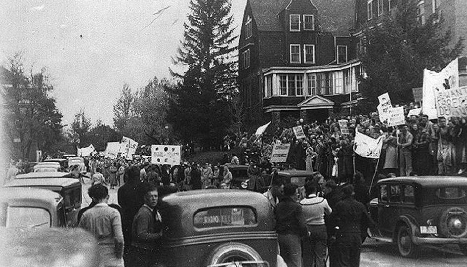 Stevens Hall 1936 strike - A scene from the 1936 student's strike protesting restrictions. Students carrying banners blockade Spokane Street the west facade of Stevens Hall.