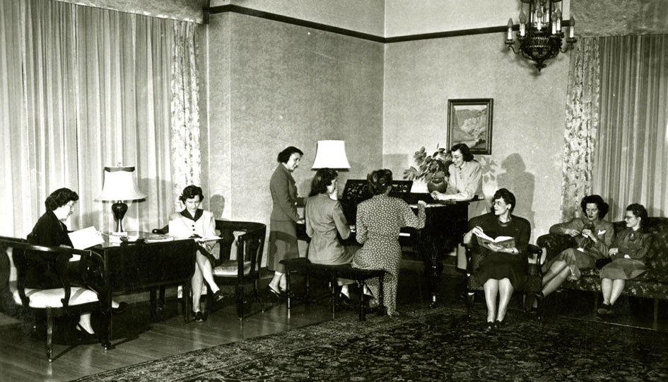 Stevens Hall drawing room scene, 1949-50. Group portrait of female students situated around piano and on couches in Stevens Hall drawing room.