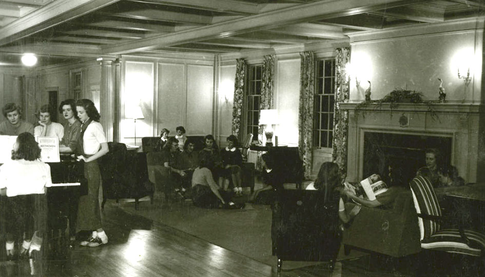Group portrait of female students situated around piano and on couches in Community drawing room, 1950.