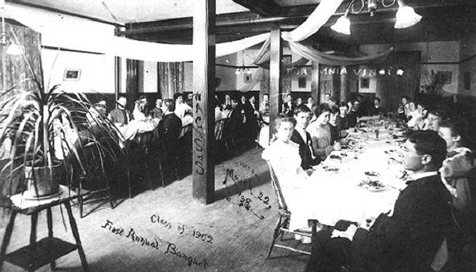 Stevens Hall Banquet, Mar. 22, 1898 - An interior view of the first annual banquet held by the Class of 1902. Dressed in formal attire alternating men and women are seated at two large tables. Banners hang from light fixtures.