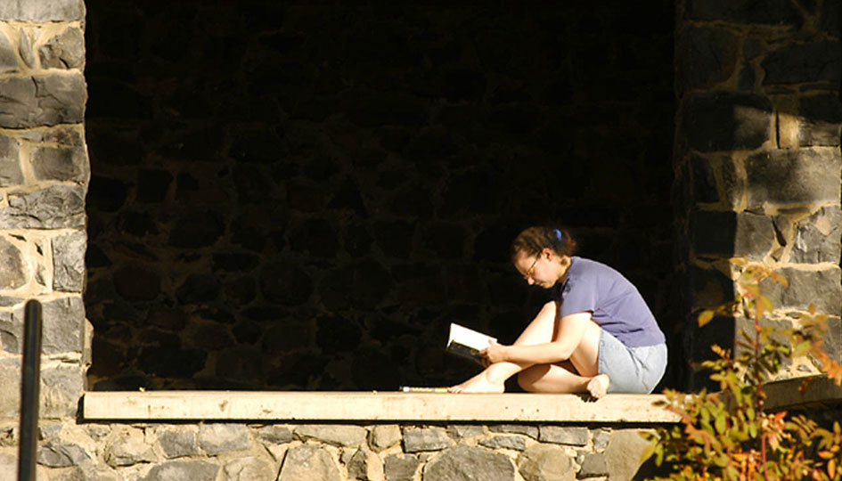 Student reading book on the back porch of Stevens Hall, 2005. Photo Shelly Hanks