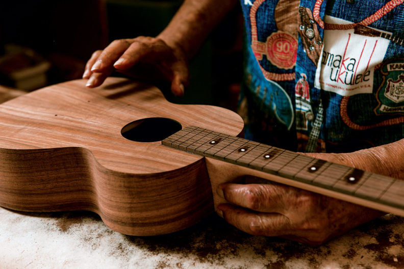 "Sam Kamaka Jr. testing the acoustic properties of an unfinished ukulele by tapping on the body, or ""tuning the top."""