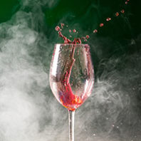 Wine glass splashing with smoke. Photo Dreamstime