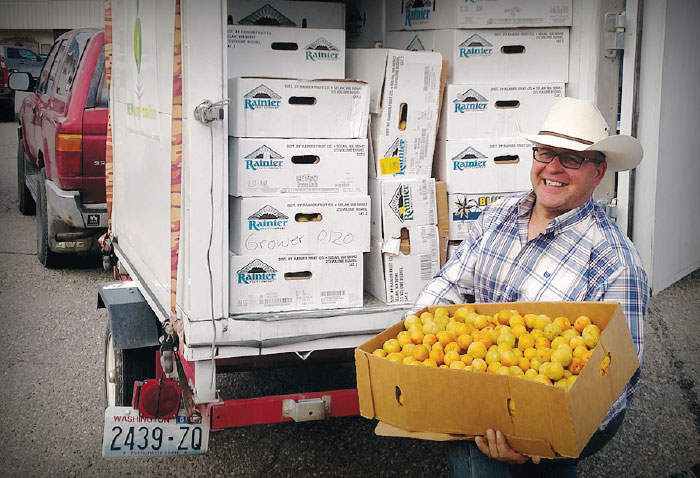 Nils Johnson carries a box of apples to put in his refrigerated trailer